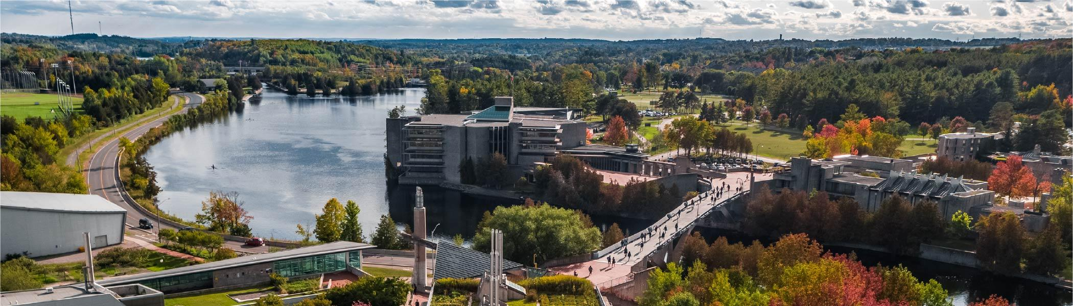Aerial photograph of Trent University. Faryon bridge in foreground, Otonabee river in left third, and Bata Library Centre.
