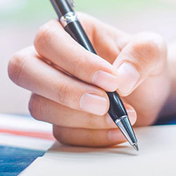 Hand holding a pen above piece of paper