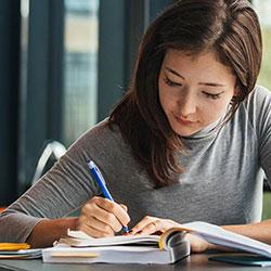 Woman sitting at desk writing