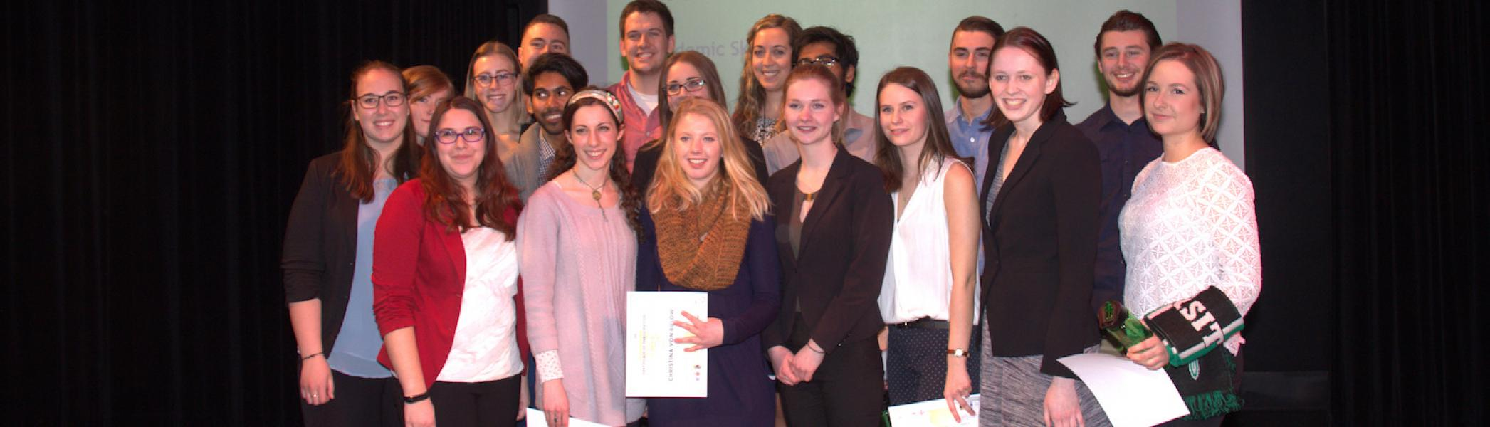 A group of students standing in a group and holding 3MP awards