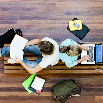 two student studying together, sitting against each other back on a university bench