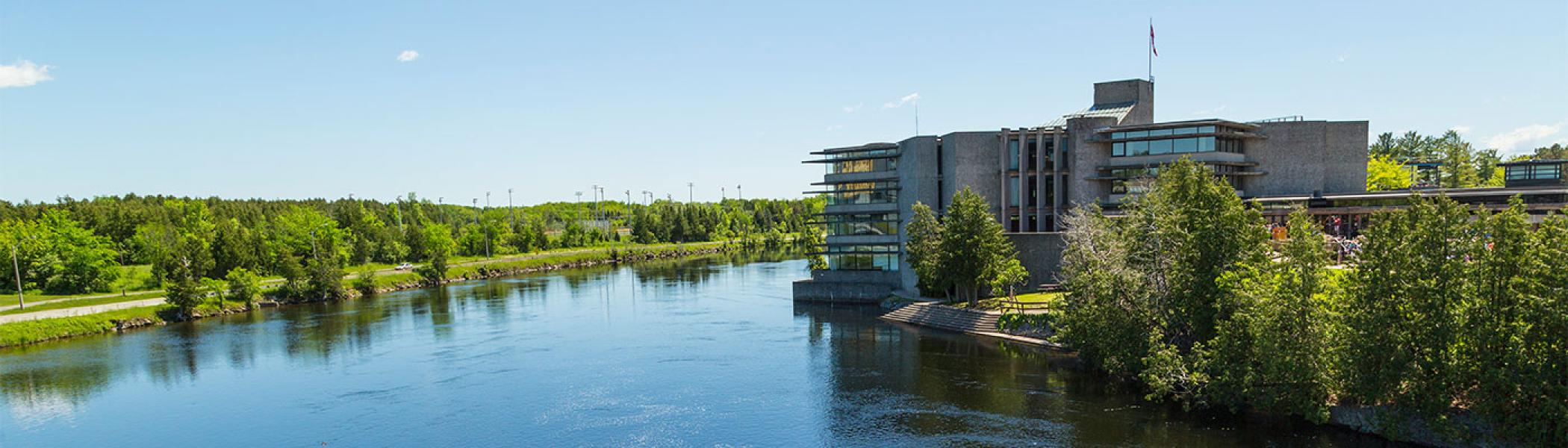 Picture of the west bank of campus from across the Otonabee river during the summer