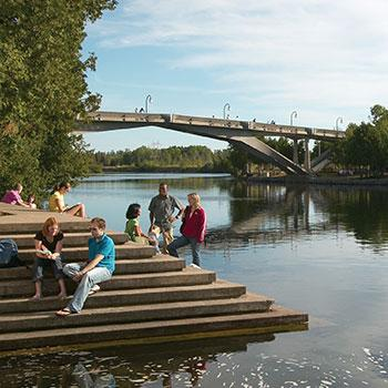 Students sitting on steps overlooking the Otonabee river on a summer day