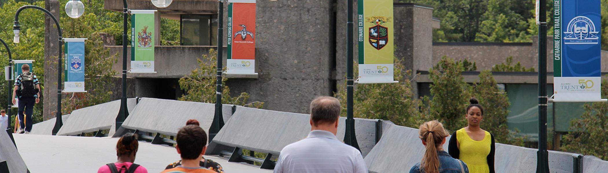 People walking across Faryon Bridge - flags of the colleges flying on bridge