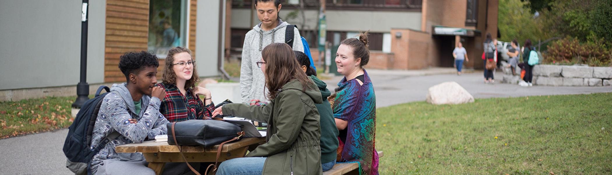 Students chatting at an outside table at Traill College