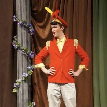 an actor on stage in a red coat and feathered hat