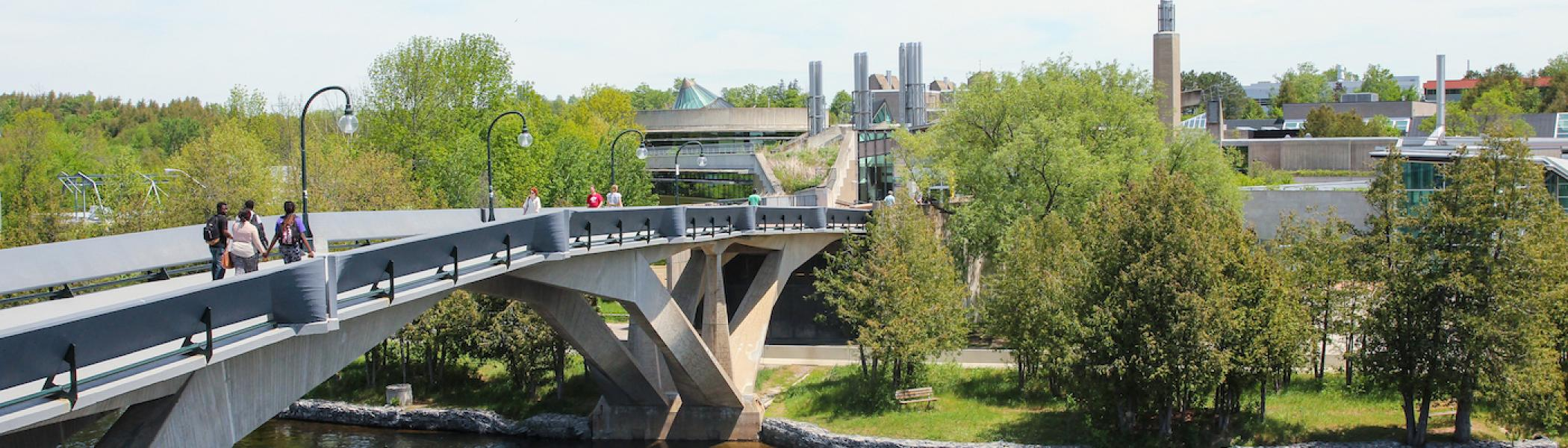 The Faryon bridge at Trent University on a sunny day with students walking across it and green trees around it