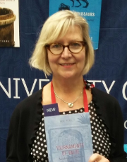 Anne Meneley holding a copy of her book Tournaments of Value
