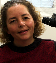 Laure Dubreuil smiling beside a microscope