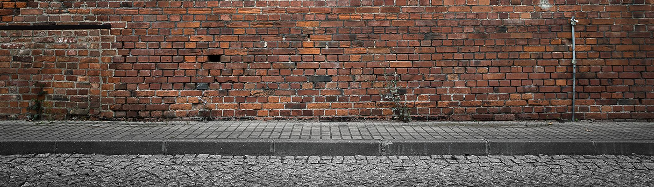 A brick wall with a grey sidewalk supporting it