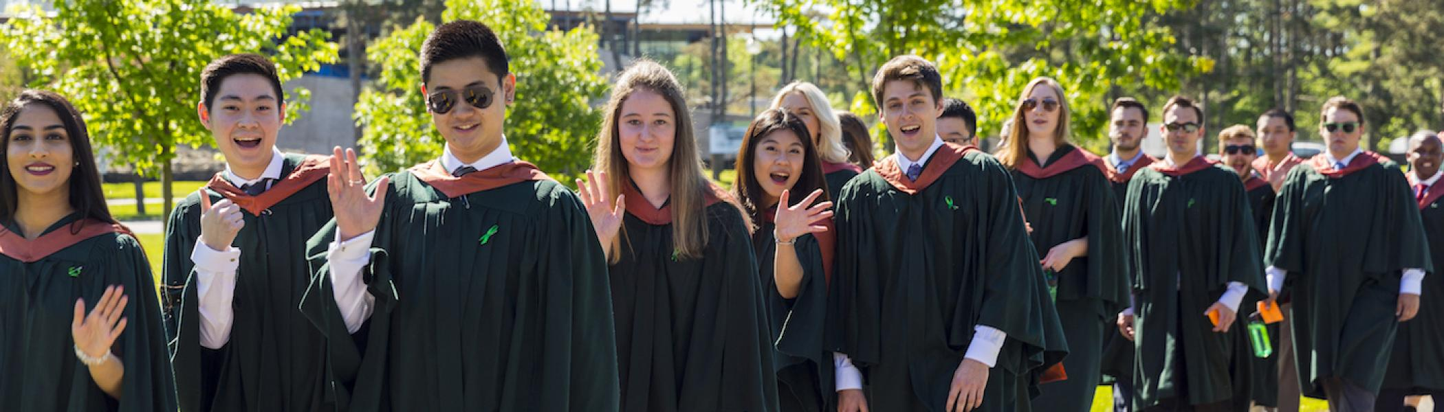 A line of graduating students on convocation day waving and smiling at the camera