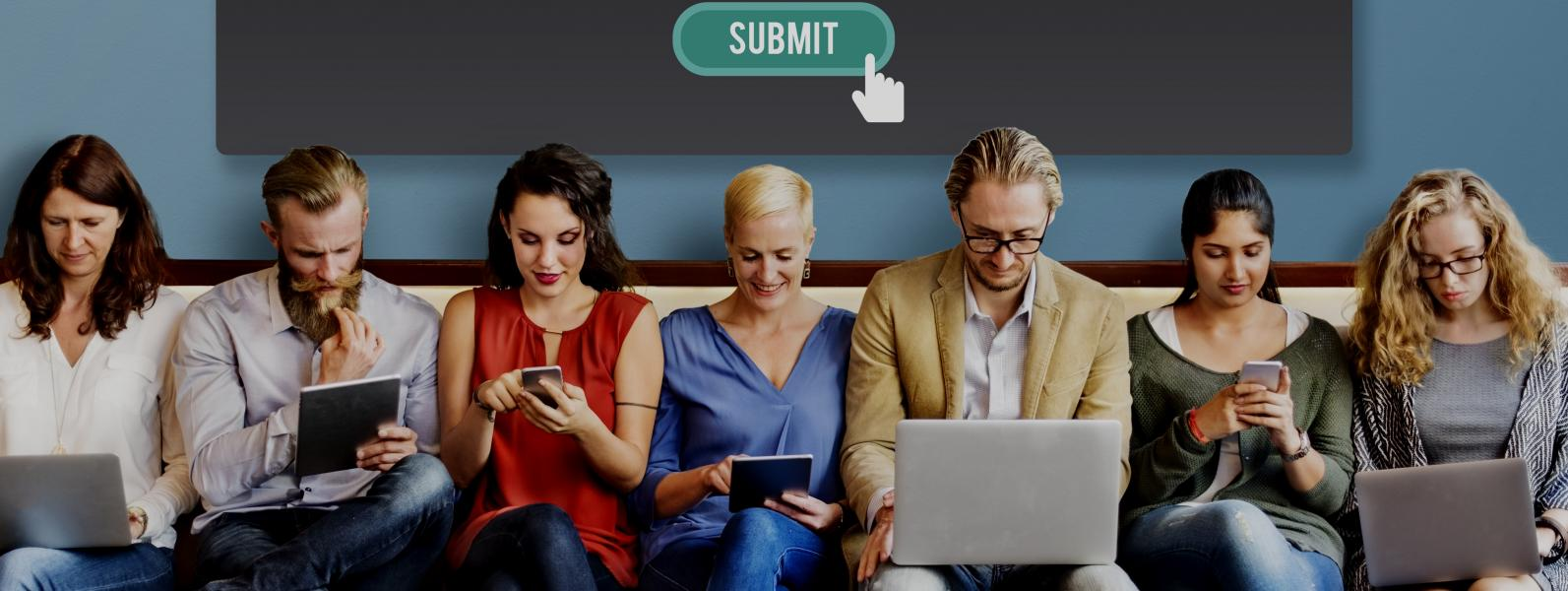 7 people sitting in a row below a sign that says Submit; using their laptops, iPads and phones
