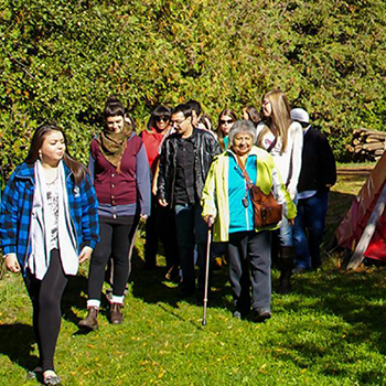 Group of students and their professor walking around the Tipi