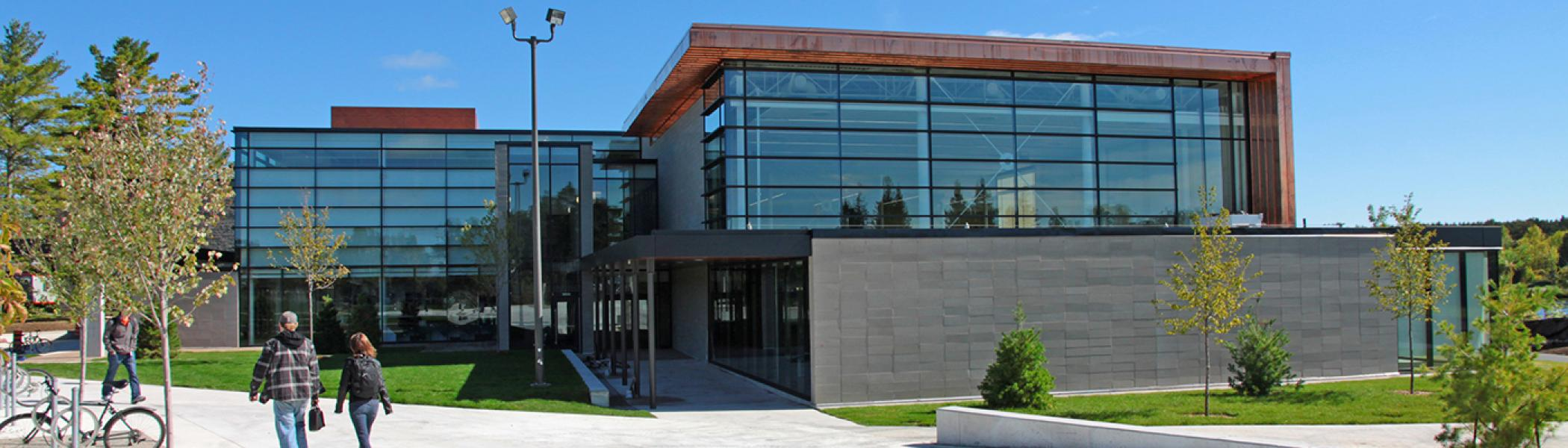 Photo of the outside of the Athletics Centre in summer. The copper features of the building contrast against the blue summer sky.