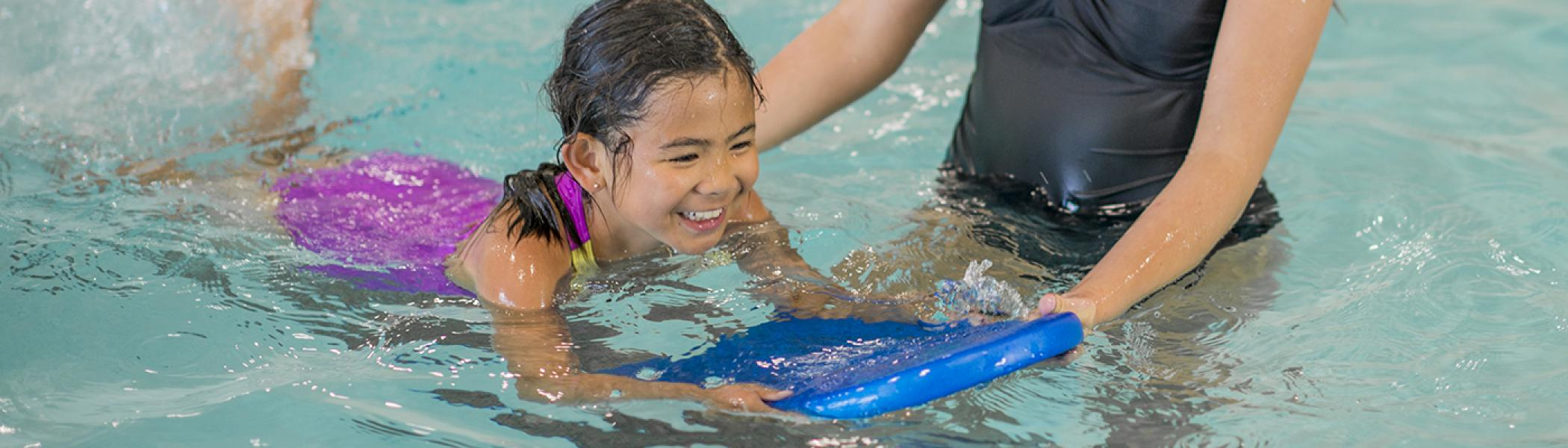 Young girl swimming on her front with a flutter board as instructor watches