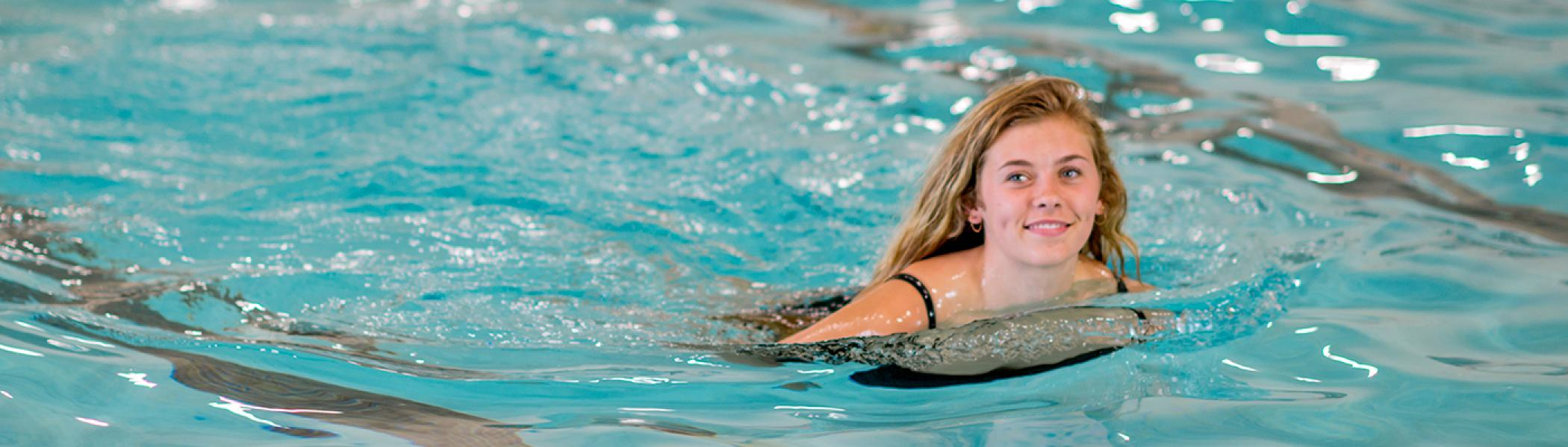 Young female Instructor swimming in the pool