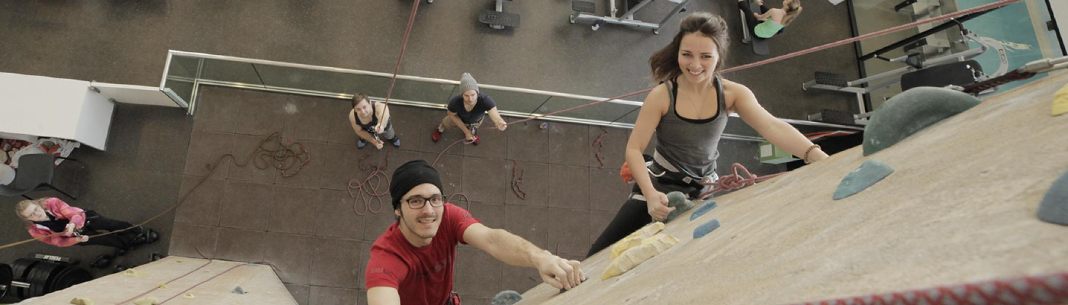 Young man and woman climbing the indoor rock wall