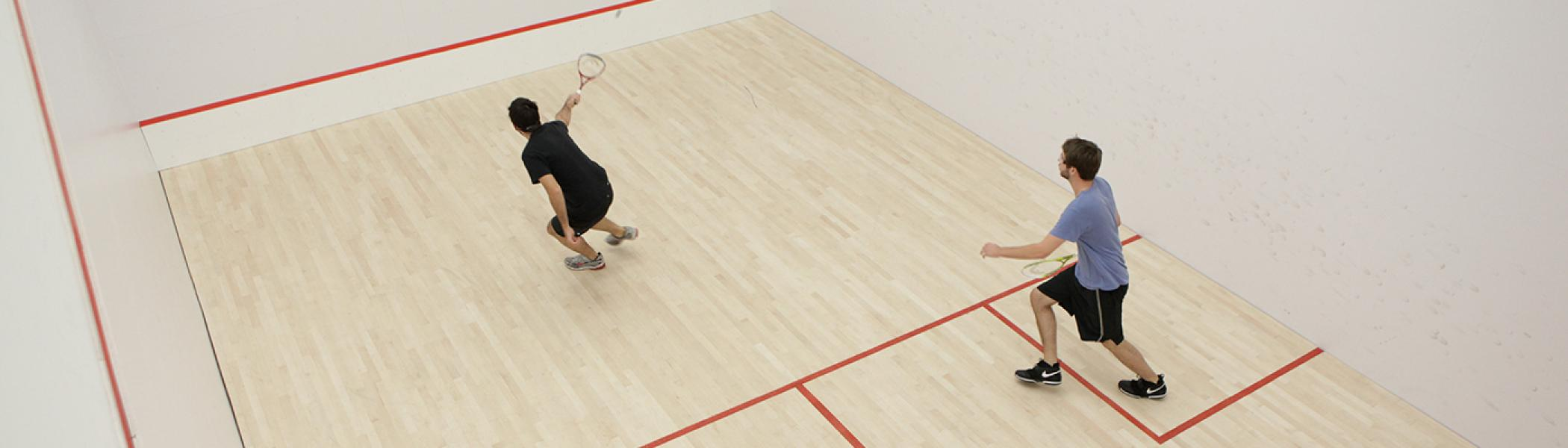 Two men playing squash on squash court