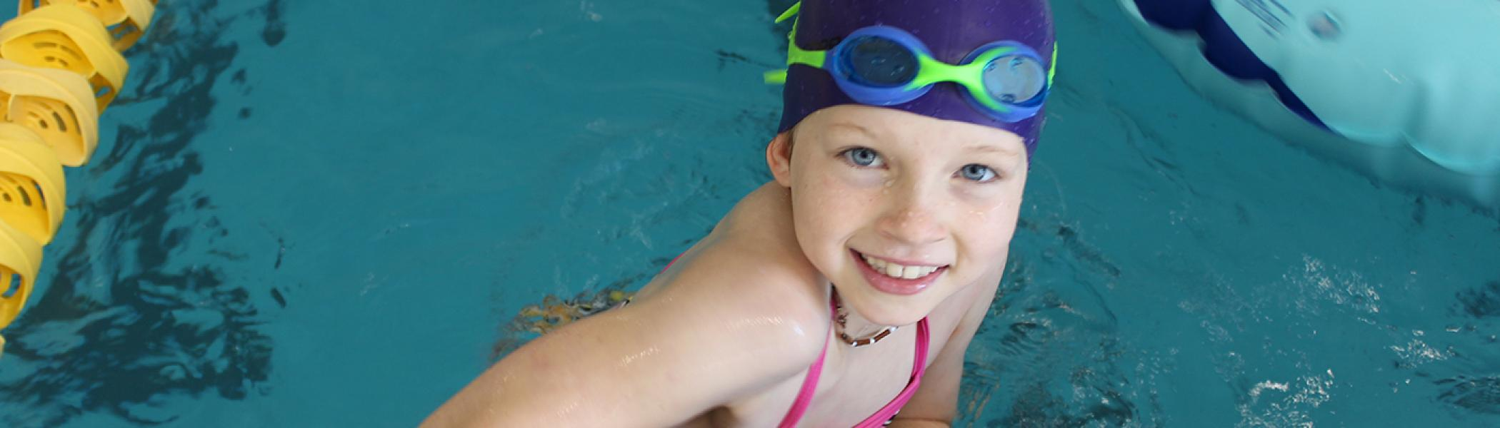 Young swimmer with bathing cap and goggles ready to swim