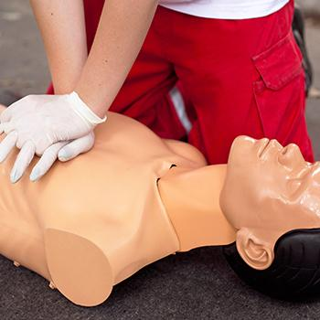 A first aid actor lays on the floor for CPR