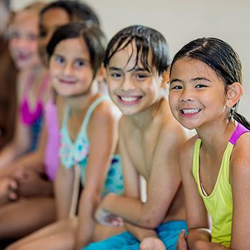 Group of happy kids sitting pool side