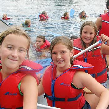 3 girls in lifejackets canoeing at Sport Camp