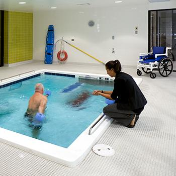 Instructor working with senior in therapy pool