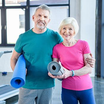 Senior couple holding yoga mats in studio