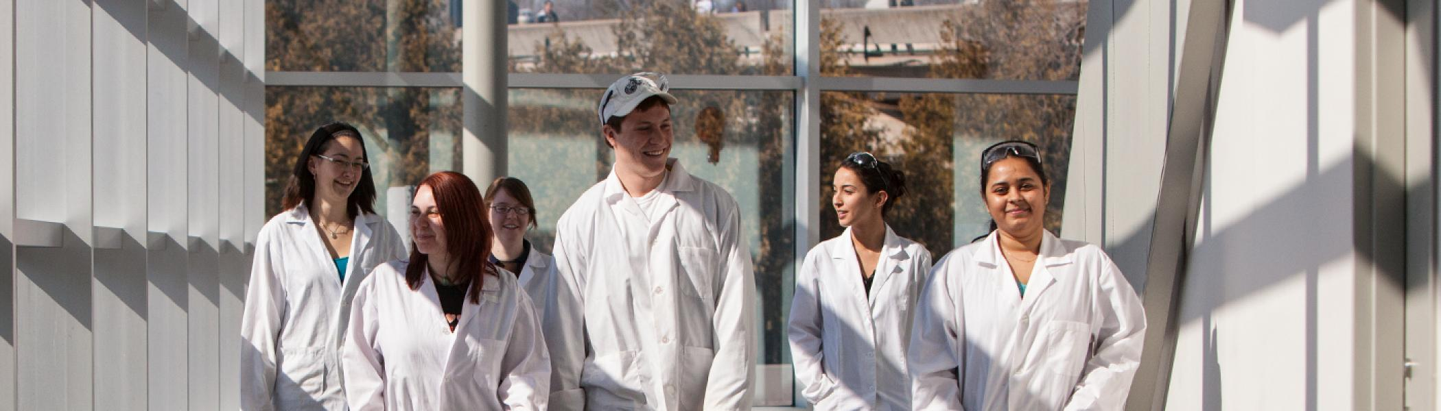 5 students walking along a hallway in white labcoats