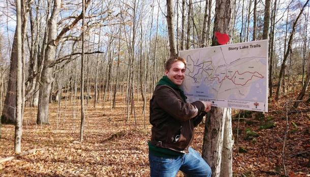 Student with trail signage in forest