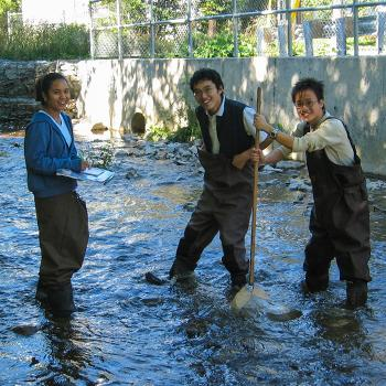 3 students standing in a river in waders smiling at the caemra in the summer shade