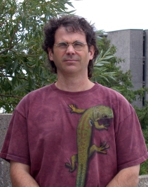Dennis Murray standing in front of trees and a building wearing glasses and a burgundy shirt with an iguana on it, squinting at the camera.