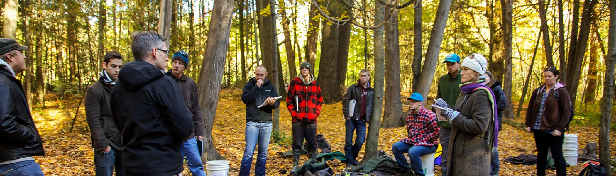 Dr. Michael Frost standing outside in the woods in the fall addressing a a group of students