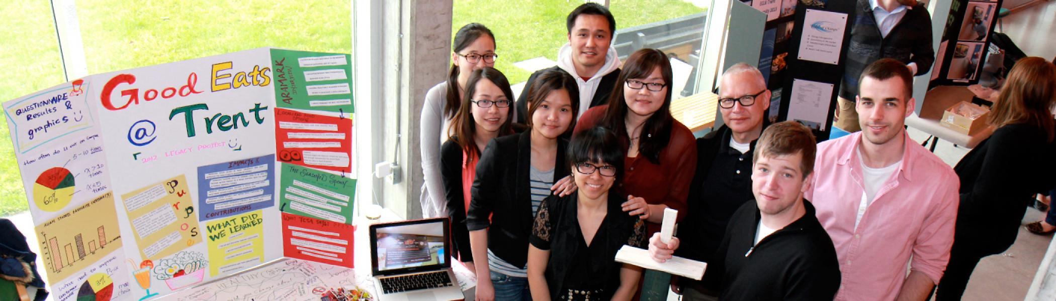 A group of students standing together looking up at the camera standing beside a table with posters and a computer on it