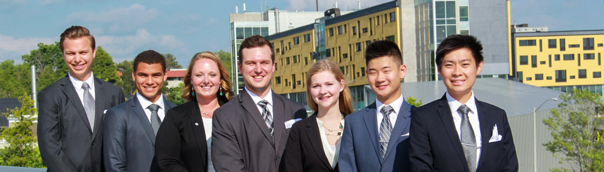 6 Students in business suits smiling at the camea standing on the Faryon bridge in the sunlight