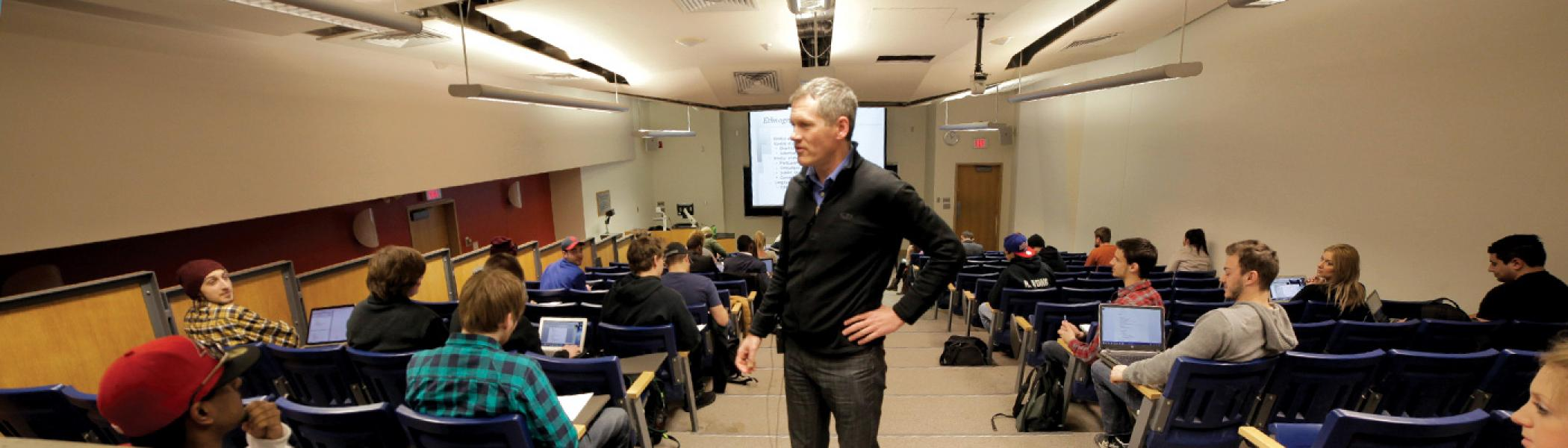 Professor Ray Dart standing in a lecture hall talking with seated students