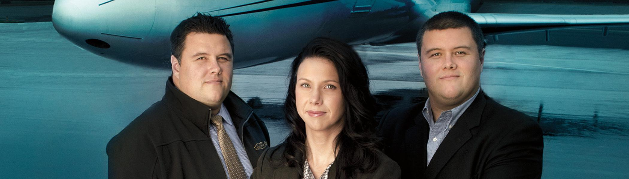 Business program alumni posing in front of a jet on a runway that they own