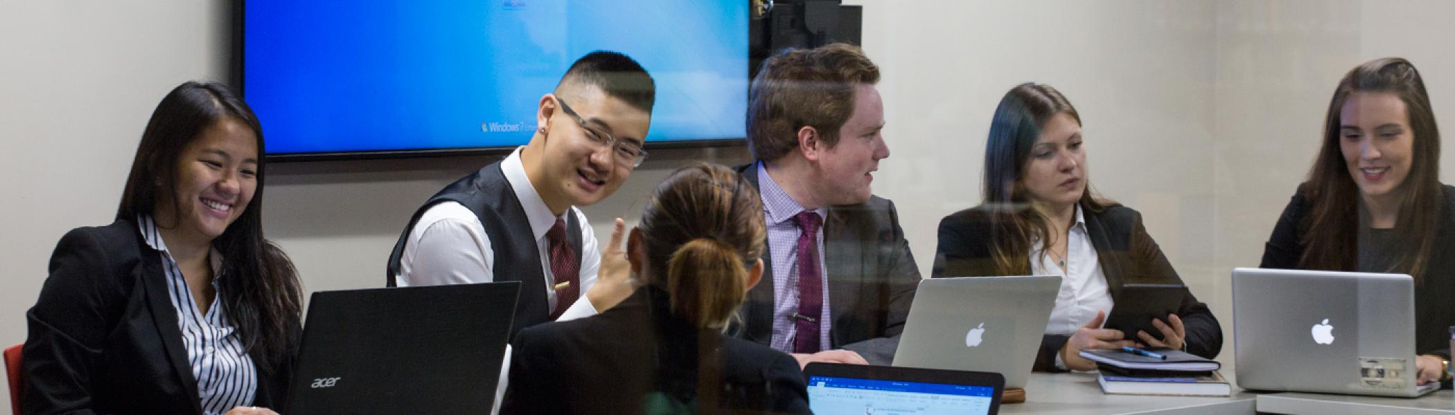 A group of students in business suits sitting at a round table in front of their laptops looking at their screens, except for one who is smiling at the camera