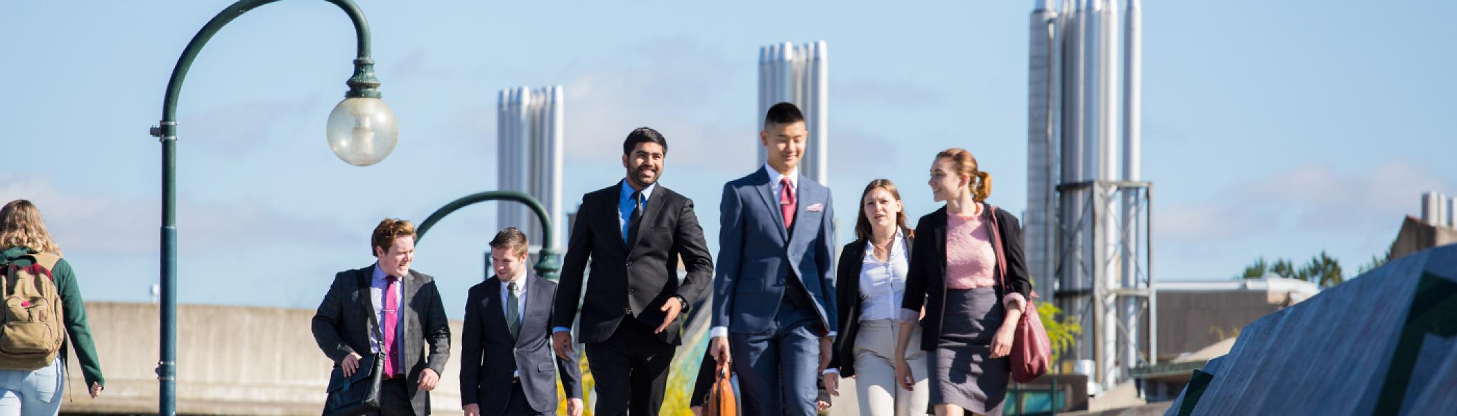 A group of students in business suits walking across the Faryon bridge in the afternoon fall sun