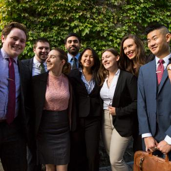 A group of students standing side by side agaist a brick wall covered in green ivy in the summer shade, wearing business suits