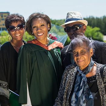 A female student in her graduation gown and copper hood standing on the Faryon bridge withe 5 family members, smiling at the camera in the summer sun
