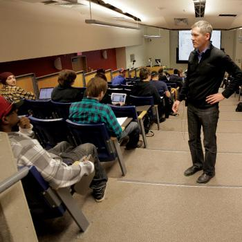 Professor Ray Dart stadning in a lecture hall talking with seated students