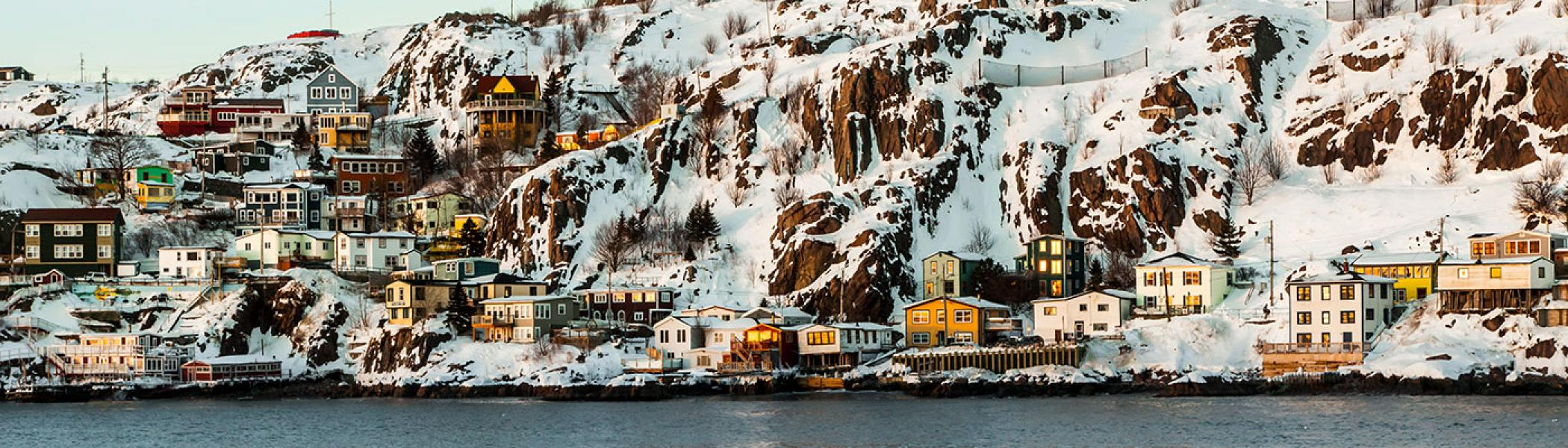 a town of colourful houses set next to water and a snowy rock-face