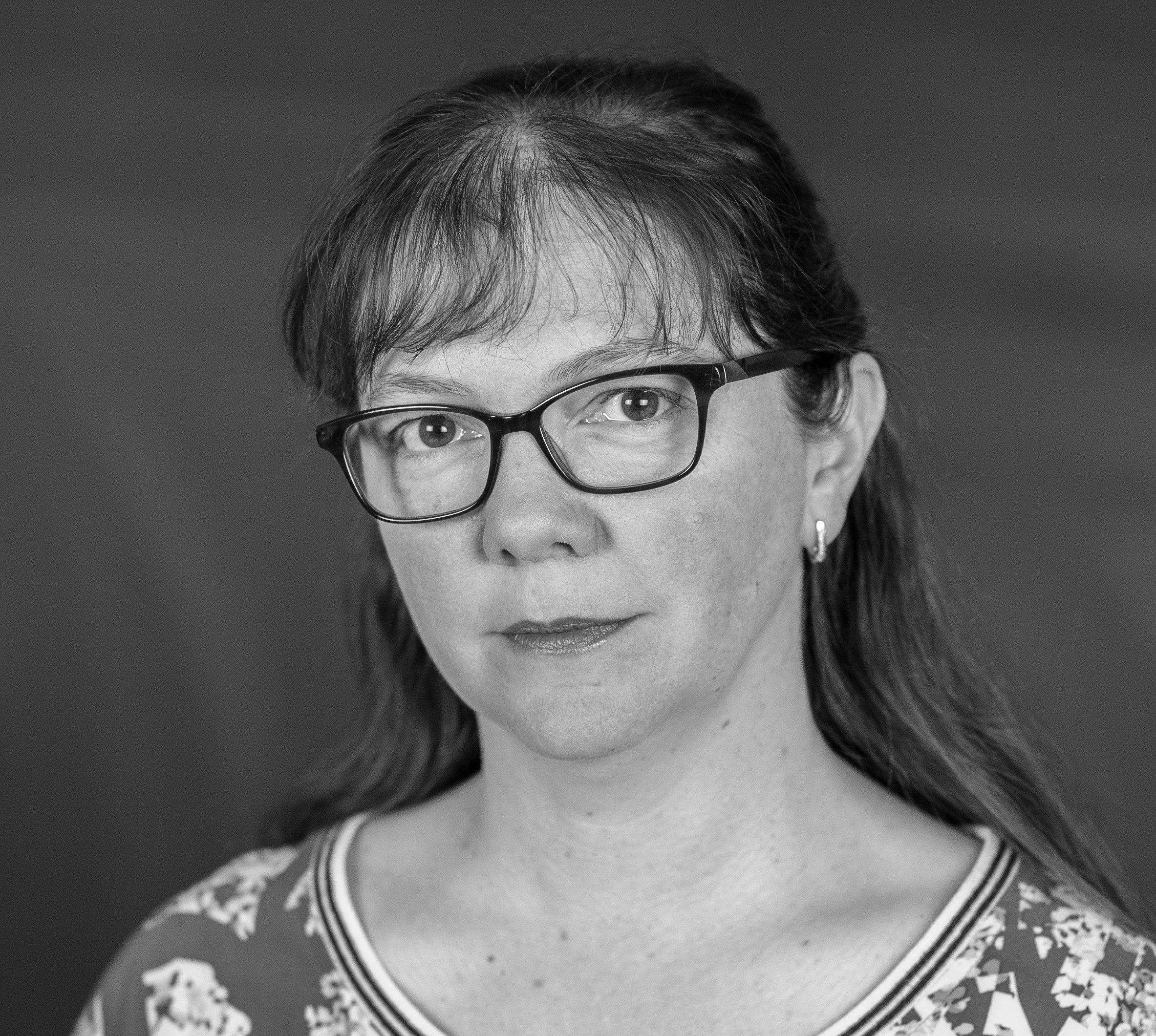 headshot of responsible looking adult, wearing glasses
