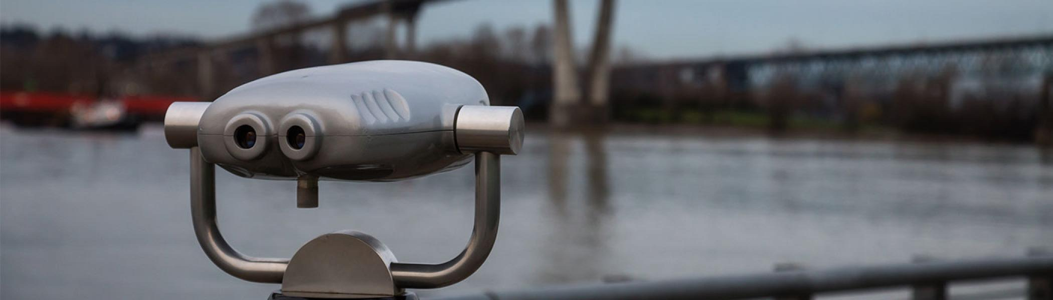 Image of a set of binoculars looking over a river at a bridge.
