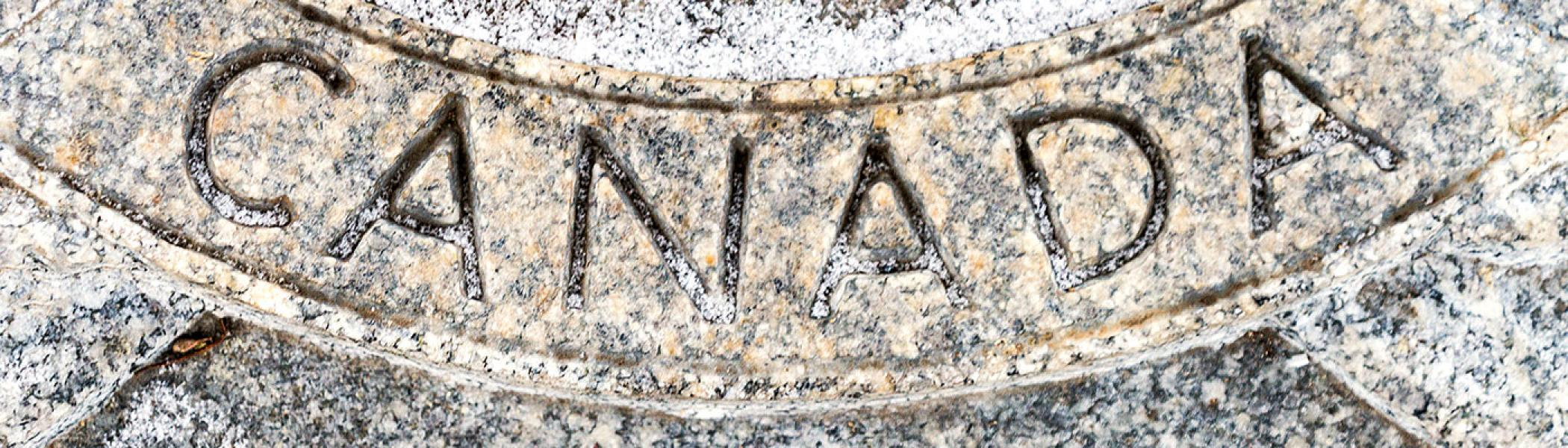 The word Canada etched into marbled stone, lightly dusted