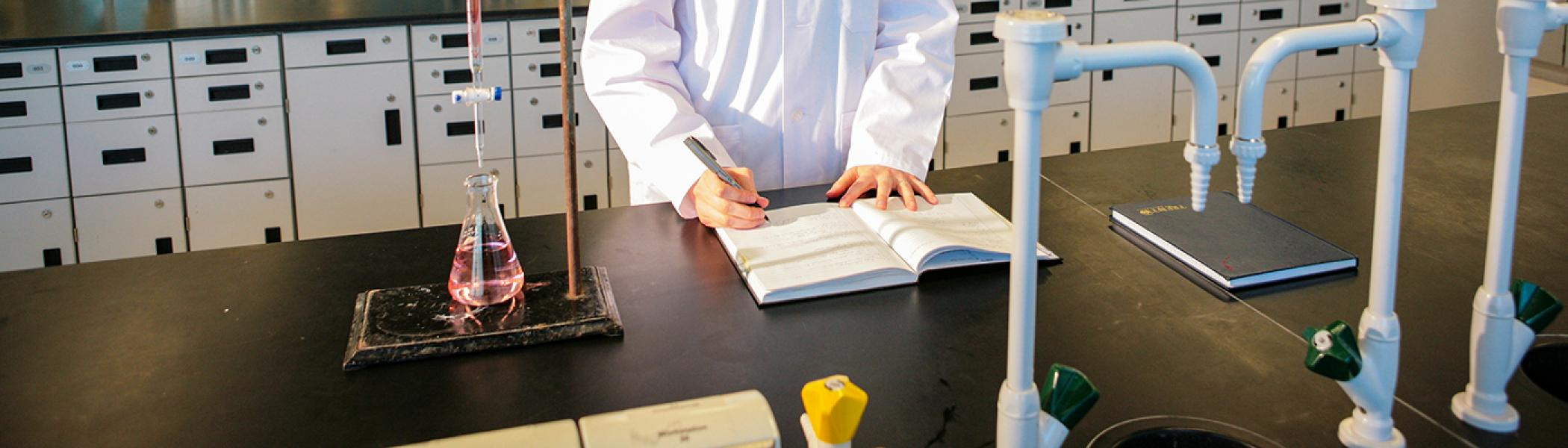 Close-up of a pair of hands writing in a lab notebook on a chemistry lab bench in front of an Erlenmeyer flask with pink liquid in it