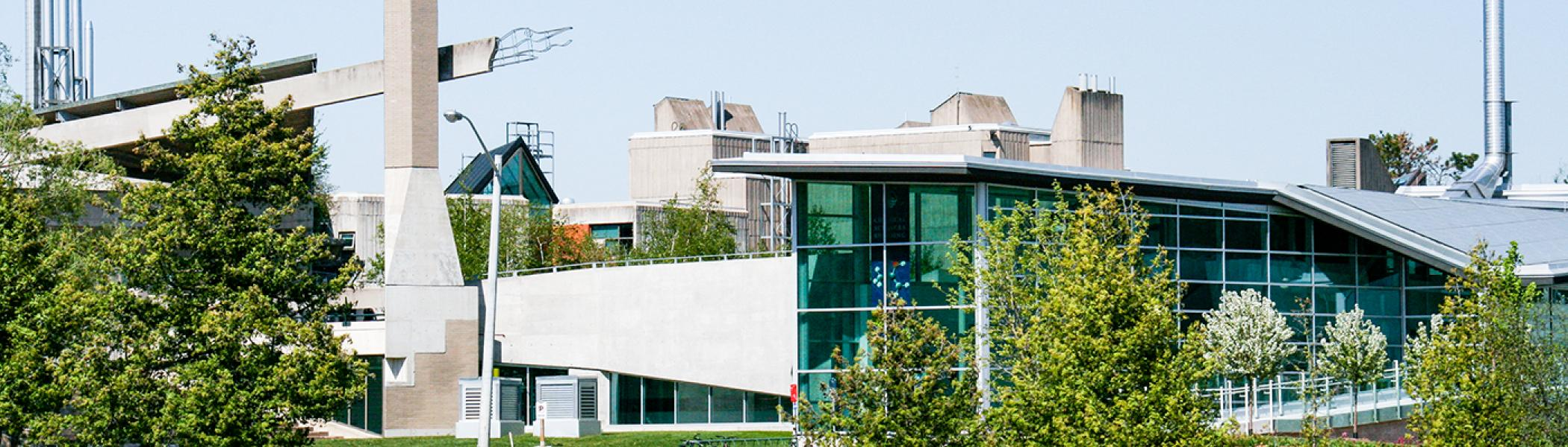 Exterior view of the Chemical Sciences Building from across the Otonabee river in the summer afternoon sun