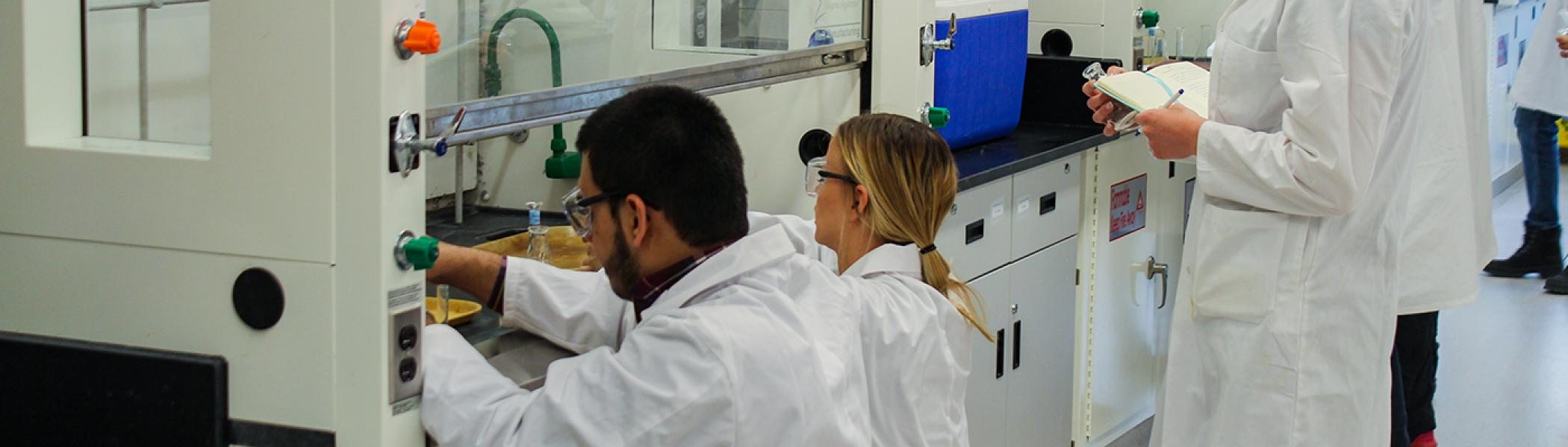 2 Chemistry students kneeling at a chemistry lab fumehood getting chemicals, wearing white labcoats and safety goggles, a 3rd student waits behind