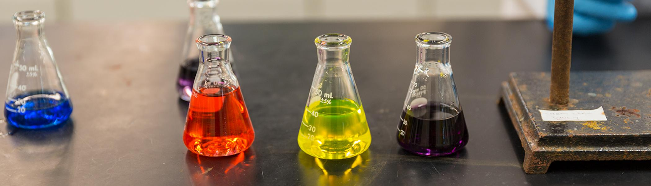 Five chemistry Erlenmeyer flasks on a black chemistry lab bench with different coloured liquids in them